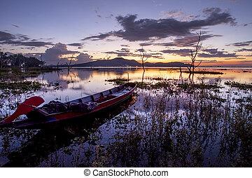 beautiful sunset sky and wood boat floating in bangpra water reservoir lake chonburi eatern of thailand