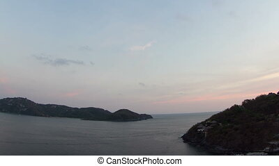 beautiful sunset time-lapse over the pacific ocean in zihuatanejo, mexico.