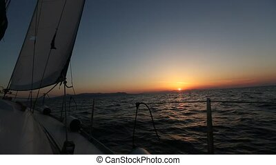 Beautiful sunset views from a sailing yacht gliding on the...