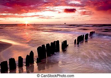 Beautiful sunset with breakwater.