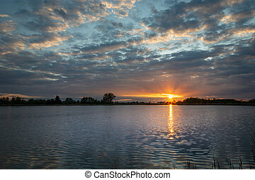 Beautiful sunset with clouds over the lake