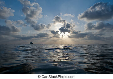 beautiful sunset with cloudy blue sky over the water of sea