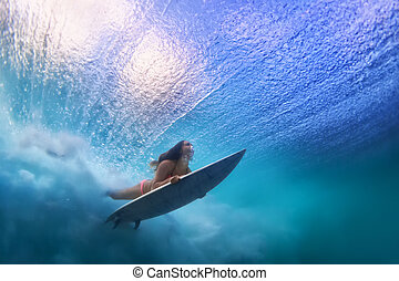 Sportive girl in bikini in action. Surfer with surf board dive underwater under breaking ocean wave. Healthy lifestyle. Water sport, swim and extreme surfing in adventure camp on summer beach vacation
