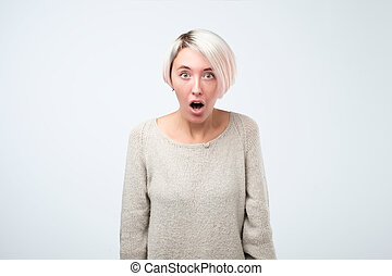 Beautiful surprised woman standing with open mouth.