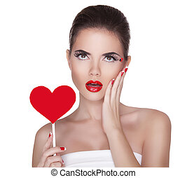 Beautiful surprised woman with glamour bright makeup holding red heart isolated on white background. Manicured nails and Red Lips.