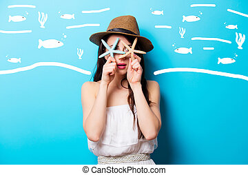 beautiful surprised young woman with starfishes standing in front of wonderful blue background
