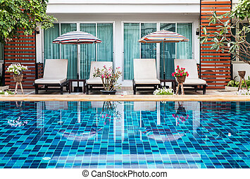 Beautiful swimming pool with chairs.