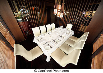 beautiful table with white tablecloth and serving and ten white chairs in empty restaurant