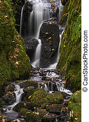 Beautiful tall waterfall flowing over lush green landscape foliage in early Autumn