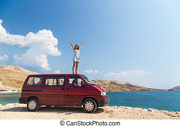 Beautiful tanned girl in a blue dress standing on a rooftop of red van and spreading arms.
