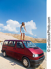 Beautiful tanned girl in a blue dress standing on a rooftop of red van.