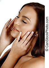 beautiful tanned Italian woman touching her face applying cream and smiling with closed eyes.