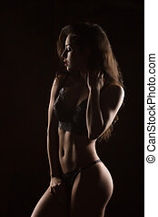 Beautiful tanned woman with body posing in lace lingerie. Shadow and light