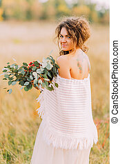 Beautiful tattoo bride with bouquet posing on the field
