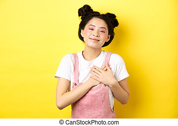 Beautiful teen asian girl in love, holding hands on heart and smiling touched, looking with affection, standing on yellow background