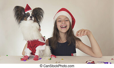 Beautiful teen girl and dog Continental Toy Spaniel Papillon in Santa Claus costumes joyfully looking around and laughing on white background