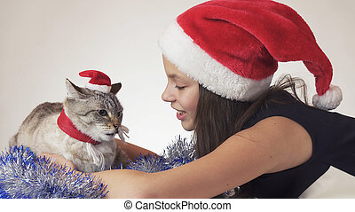 Beautiful teen girl and her cat in Santa Claus caps joyfully hugging on white background