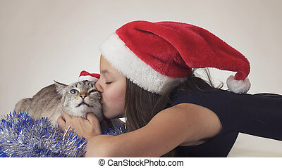 Beautiful teen girl and her cat in Santa Claus caps joyfully kissing on white background