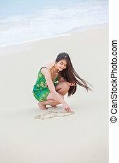 Beautiful teen girl drawing heart in sand on tropical beach