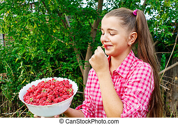 teen girl holding a bowl of raspberries in the garden