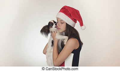 Beautiful teen girl in a Santa Claus cap and dog Continental Toy Spaniel Papillon joyfully kissing and fooling around on white background