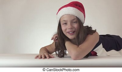 Beautiful teen girl in a Santa Claus hat laughs on white...