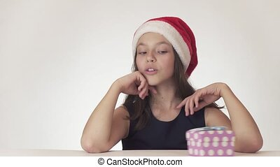 Beautiful teen girl in a Santa Claus hat dreams of a gift,...