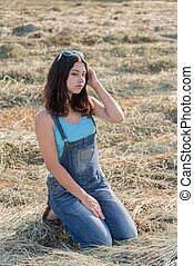 Beautiful teen girl in field with straw