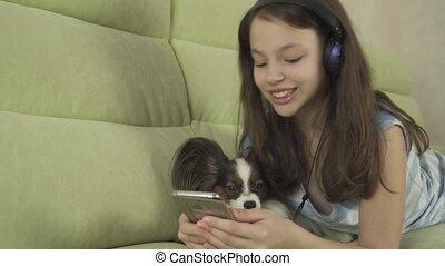 Beautiful teen girl in headphones singing karaoke songs in...