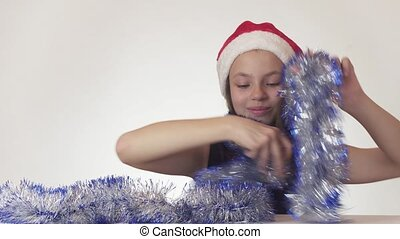 Beautiful teen girl in Santa Claus hat and New Year's tinsel happily and mischievously dances on white background stock footage video