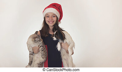 Beautiful teen girl in Santa Claus hat hugs her cat and dog on white background