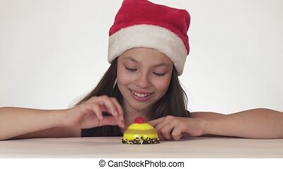 Beautiful teen girl in Santa Claus hat with an appetite and pleasure eating a birthday cake on white background stock footage video