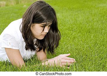 beautiful teen girl lying on grass