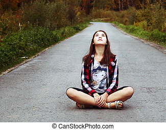 beautiful teen girl sit on the country empty road
