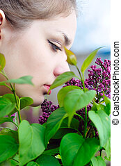 teen girl smelling lilac blossoms