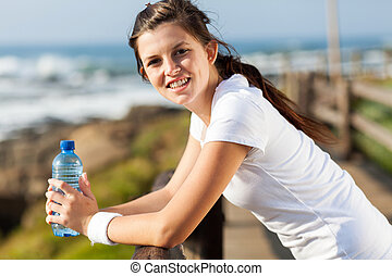 beautiful teen girl with water bottle after exercise