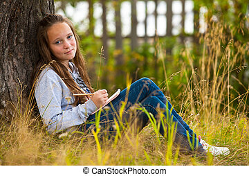 Beautiful teen-girl writing in a notebook while sitting in the park (looks into the camera)