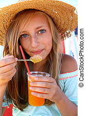 Beautiful teen with an iced drink, straw hat on beach