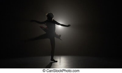 Beautiful teenage ballerina girl dreaming of a ballet career while rehearsing graceful moves in a dark studio in slow motion