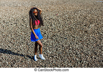 Beautiful teenage black girl in blue skirt and pink bra on the rock beach.