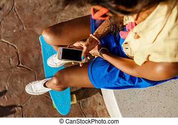 Beautiful teenage black girl in blue skirt sit with her...