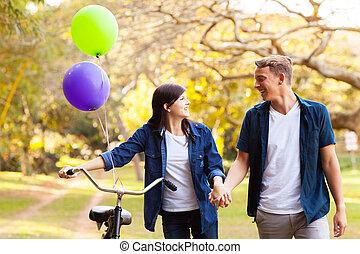 teenage couple walking in park