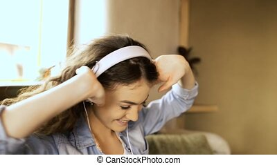 Beautiful teenage girl at home sitting on couch, laptop on...
