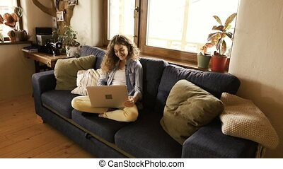 Beautiful teenage girl at home sitting on couch working on laptop.