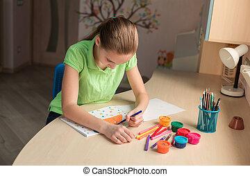 Beautiful teenage girl drawing at the table