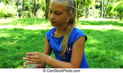 teenage girl in a park drinking water
