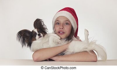 Beautiful teenage girl in Santa Claus hat happily hugs her dog on white background stock footage video