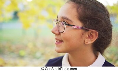 Beautiful teenage girl looking away in autumn park, slow ...