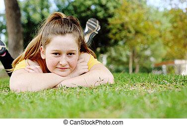Beautiful teenage girl lying on green meadow in city park