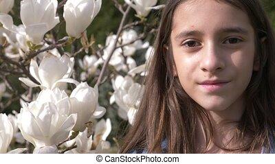 Beautiful teenage girl on white magnolia flowers background...